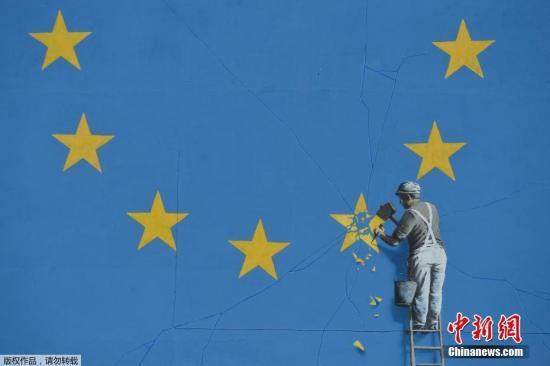 资料图:当地时间2018-11-19,英国多佛,一名街头艺术家班克西创作了一幅画,画面中一名工人正从欧盟12星旗帜上抹掉一颗星,寓意着英国将脱离欧盟。