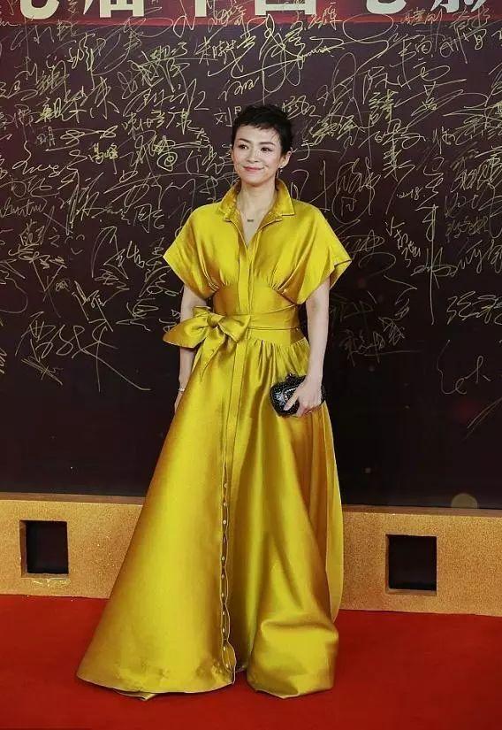 章子怡留着短发,穿着一身金色长裙,手拿黑色手包,乍看上去很有蒋雯丽