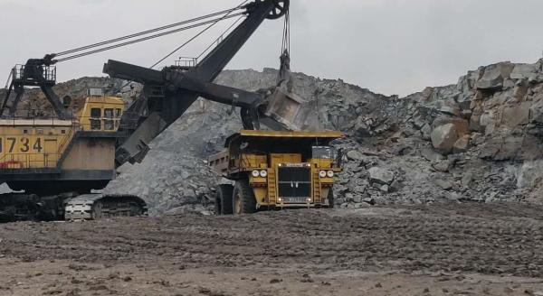 矿区正在用电铲和卡车进行作业,右边的重型卡车宽4米,高6米澎湃新闻记者徐路易摄 露天开采出来的煤炭通常被装在运输车辆或输送带上,运到煤矿外面,再换一辆卡车运去压碎。贺永顺向记者介绍,矿上之前还详细规划过是否可以用电动车等更环保的运输设备将煤炭运出矿区,考虑到充电尚不够便捷以及露天矿本身的特点,便搁置了这一想法。 露天矿的整体作业范围是随着我们的勘探而不断移动的,贺永顺指向西面,西排土场已现点点绿色,目前正在进行生态复垦和植被种植, 以前那里才是矿坑,现在已经移到我们脚下了。 根据中煤平朔生态环境治