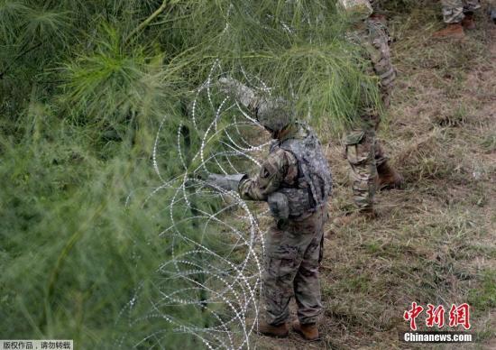 资料图:美国士兵在美墨边境安装铁丝网,严防移民入境。