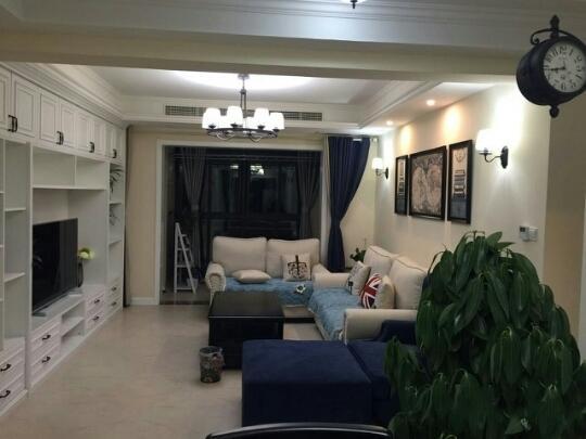 客厅地面铺贴瓷砖,沙发靠墙呈围合状摆放,背景墙上三幅装饰画和两盏